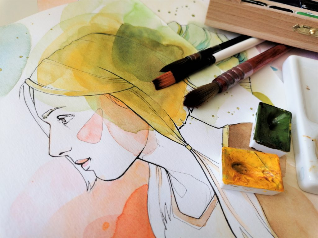 Paintbrushes and watercolour paints positioned on top of a portrait of a young woman.