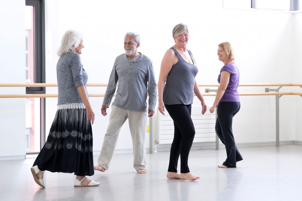 A man and three women wearing casual clothes standing in a dance studio smiling.