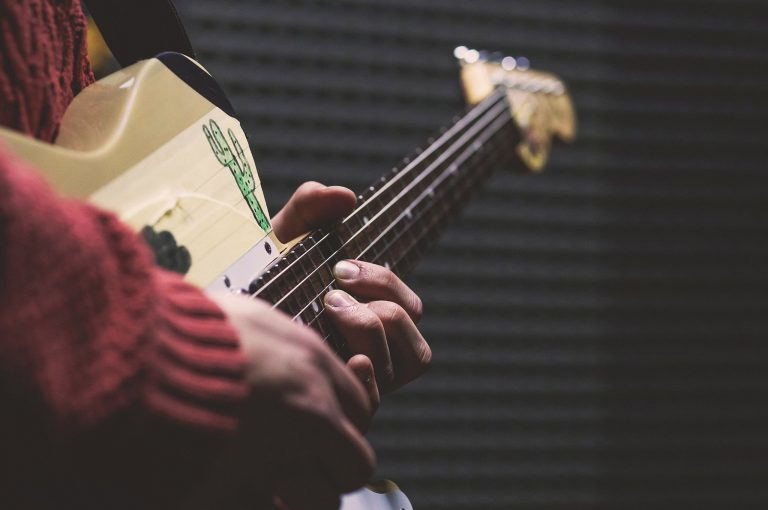 Close up images of a person holding a guitar with fingers on the strings.