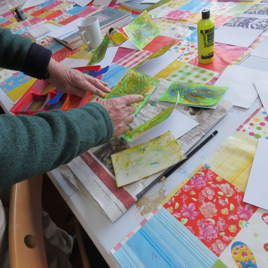 Close up of two hands with brightly coloured art work.