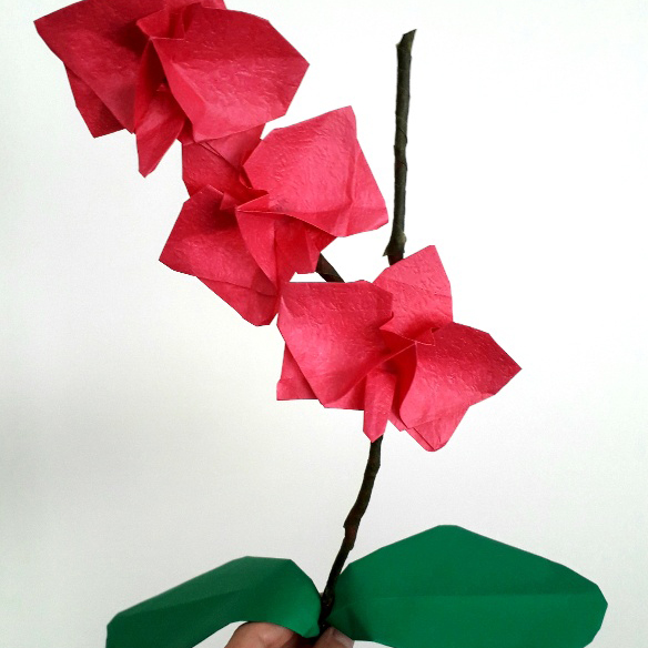 Pink paper flower on a stalk with two leaves.