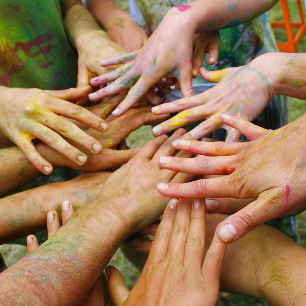 Multiple pairs of paint marked splayed hands gathered together.