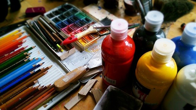 Bottles of paint, a watercolour paint set, brushes and coloured pencils.
