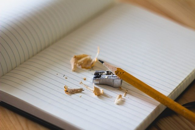Blank lined note pad with a pencil, sharpener and pencil sharpenings.