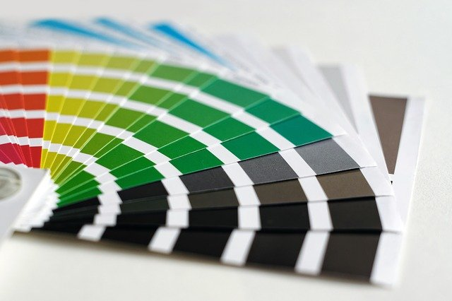 A fanned out selection of coloured paint charts.