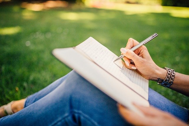 Close up of a woman sitting on grass writing in a notebook.